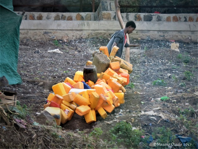 Boy dragging empty plastic bottles