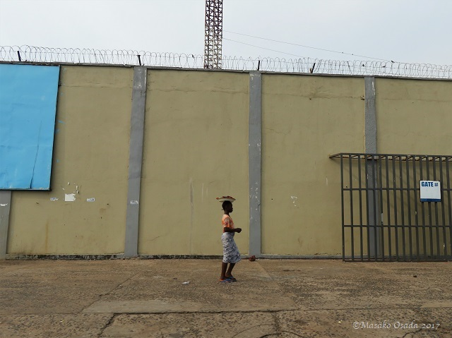 Girl walking in front of heavy-security building, Monrovia, Liberia, April 2017