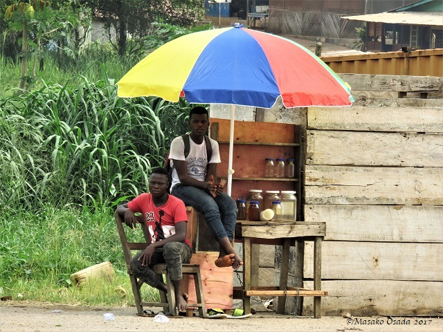 Two men under umbrella, Bong Town, Liberia, April 2017