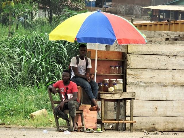 Two men under umbrella, Bong Town, Liberia, April 2017