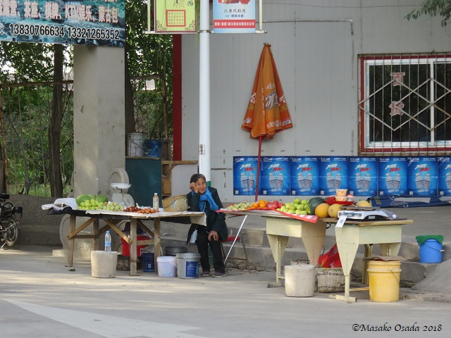Fruit seller. Overhanging Great Wall, Jiayuguan, Gansu, September 2018